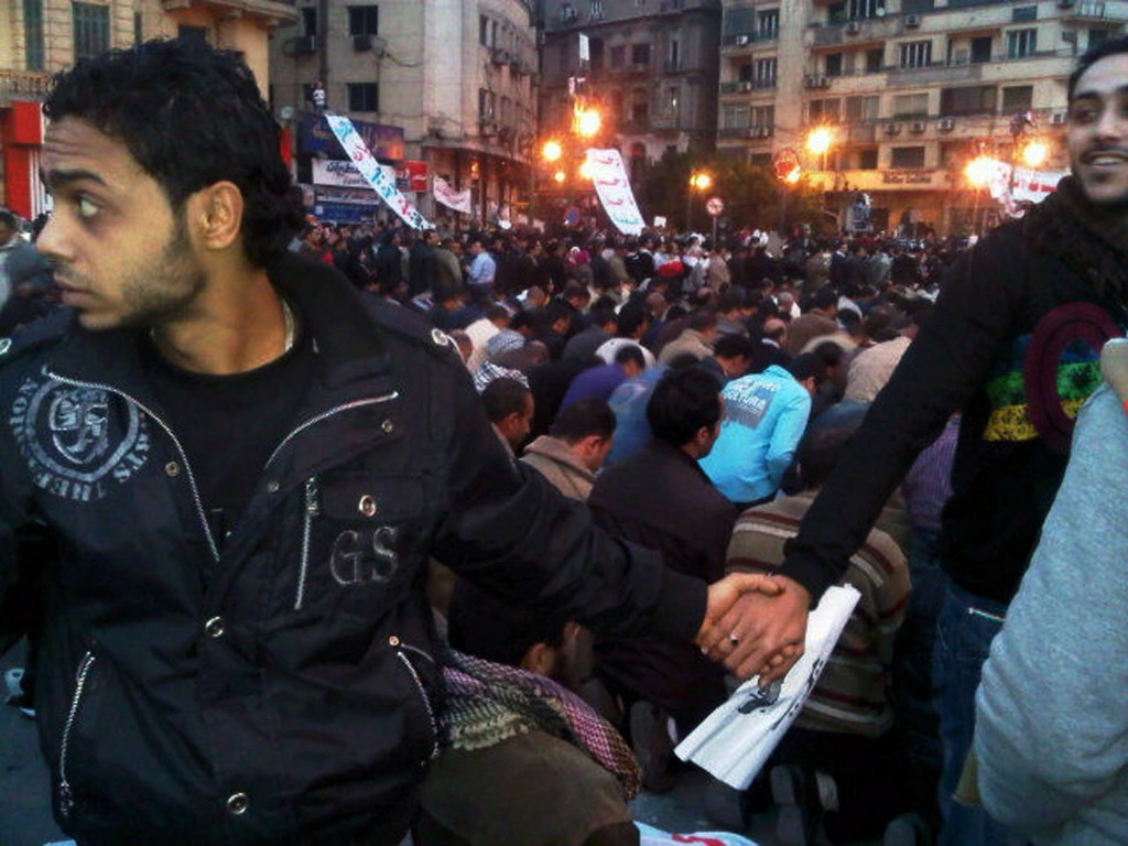 christians protecting muslims in prayer at Tahrir Square